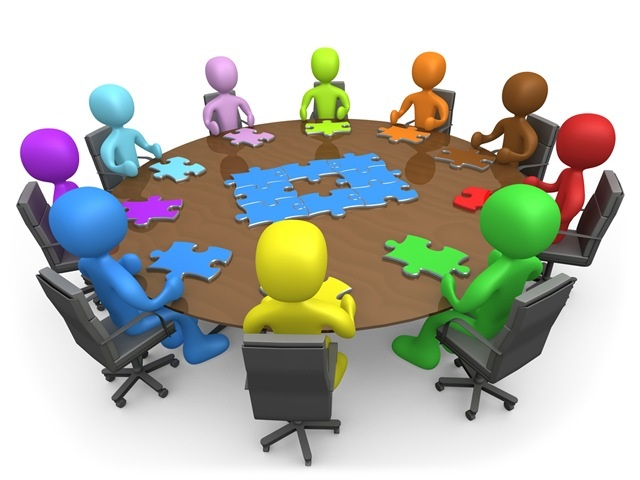 Image of people sitting around a table putting puzzle pieces together